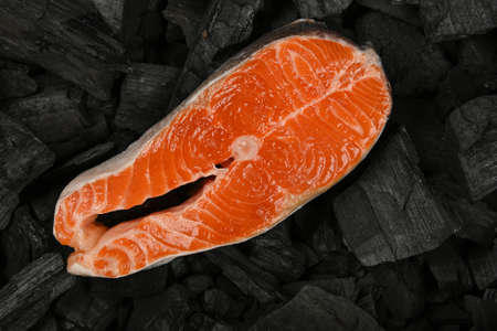 Close up raw salmon fish steak on black lump charcoal pieces ready for barbecue grill cooking, elevated top view, directly above