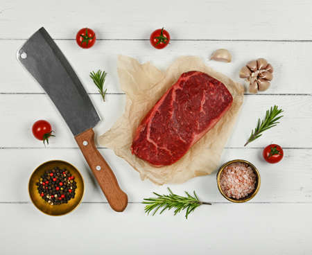 Close up one aged prime marbled raw sirloin beef steak on brown paper parchment wrapping, with cleaver knife and spices, over white wooden table background, elevated top view, directly above