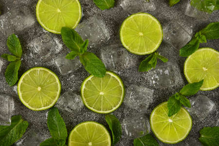 Close up flat lay of lime slices, fresh green mint leaves and ice cubes on grunge gray stone table surface, elevated top view, directly above Stok Fotoğraf