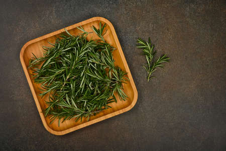 Close up fresh green rosemary leaves on bamboo wooden plate on table, elevated top view, directly above Stok Fotoğraf