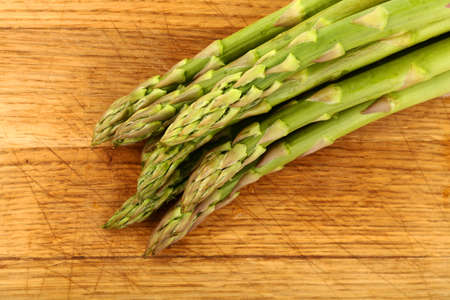 Close up bunch of fresh green asparagus on wooden cutting board, elevated top view, directly above