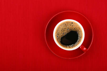 Close up one cup full of black instant frothy coffee on saucer over red tablecloth, elevated top view, directly above