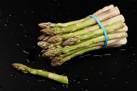 Close up bunch of washed fresh green asparagus on black table with drops of water, high angle view Stok Fotoğraf