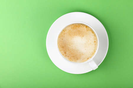 Close up one full white cup of frothy latte cappuccino coffee and saucer over pastel green paper background, elevated top view, directly above