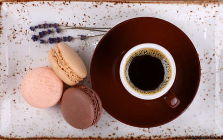 Close up three French macaroon cookies and cup of black coffee on served on brown saucer and rustic porcelain plate, elevated top view, directly above