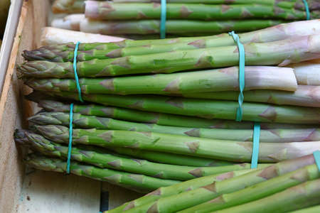 Bunch of fresh green asparagus shoots in wooden box of retail market display, close up, high angle view Stok Fotoğraf