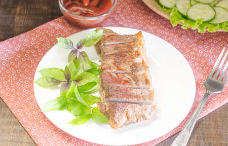 salad decoration: Grilled beef steak with salad and souce on wooden table at white plate. Salad with tomatoes and cucumbers and souce barbecue. Leafs of basil as decoration.