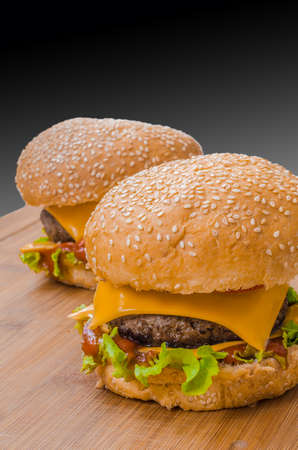cheeseburgers: Two tasty cheeseburgers with lettuce; beef; double cheese and ketchup. Shallow focus.