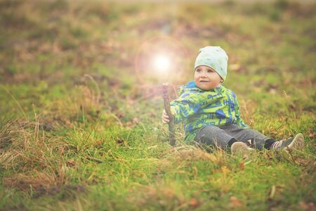 Small boy is sitting on grass and holding magic wand with light out of it