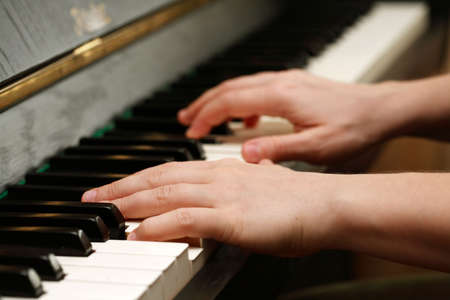 Hands playing piano photo