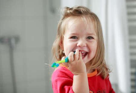 Pequeña niña lavándose los dientes en el cuarto de baño  Foto de archivo - 1134283