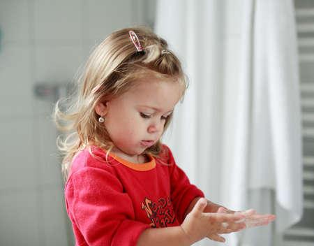 Pequeña niña lavándose las manos en el cuarto de baño  Foto de archivo - 1134281