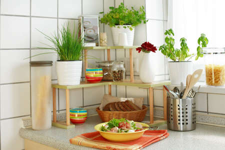 potherb: Kitchen interior with small shelf with pot-herb and kitchen implements Stock Photo