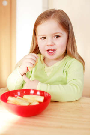 Beautiful small girl eating fruit Stock Photo