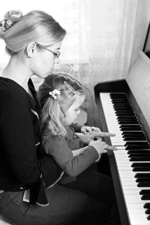 tocando el piano: Madre y ni�o que juegan el piano