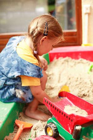enfant qui joue: Enfant jouant dans le sandbox