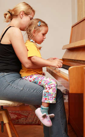 Mother and daughter play piano Stock Photo