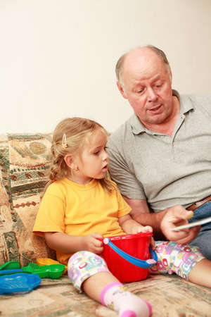 educating: Grandpa and grand-daughter reading and playing Stock Photo