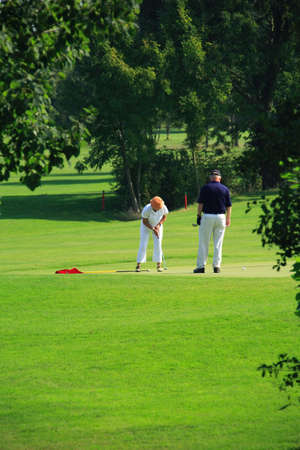 Two seniors playing golf photo