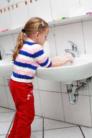 lavandose las manos: Peque�a ni�a lav�ndose las manos en el ba�o  Foto de archivo