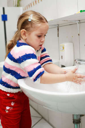 washing hand: Small girl washing her hands in the bathroom