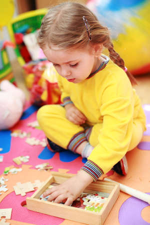 baby playing toy: Cute child playing with puzzle