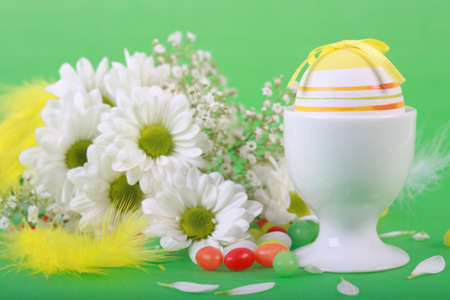 Photo of Easter eggs and flowers on green background photo