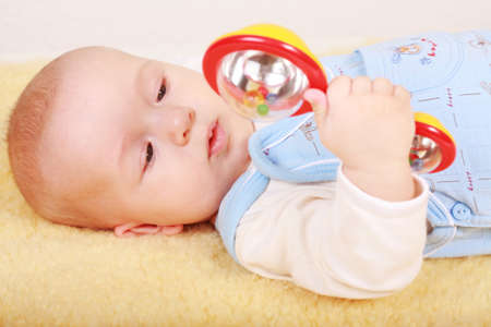 l natural: Portrait of cute newborn playing with rattle