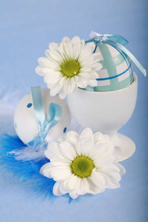 Photo of Easter eggs and flowers on blue background photo