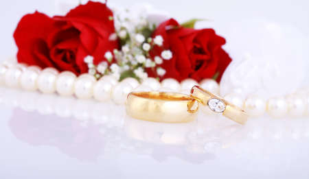 Still life with golden wedding rings and red roses photo