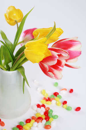 Home appliance - beautiful tulips in vase on the table with small Easter eggs photo