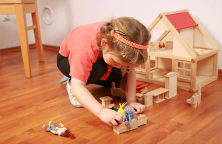 role play: Cute little girl plays with dolls house Stock Photo