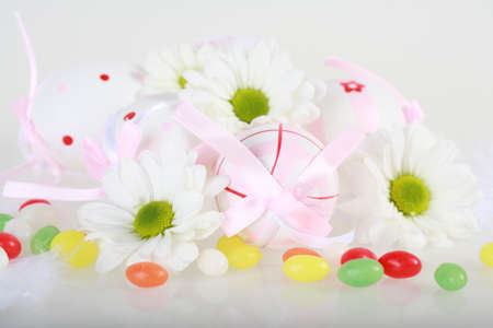 Photo of Easter eggs and flowers on white background photo