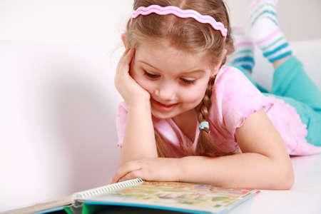 sincere girl: Cute little girl reading a book