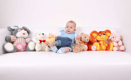 plush toy: Portrait of cute baby with plenty of toys Stock Photo