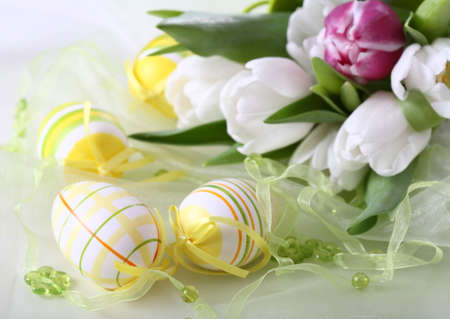 Table decoration for Easter with eggs and white tulips