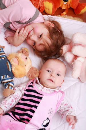 Cute older sister with small baby and toys Stock Photo - 4422085
