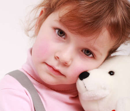 cuddly baby: Portrait of sad little girl with teddy