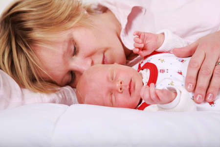 Lovely newborn sleeping with his mother