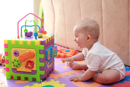 Portrait of cute newborn playing with toys photo