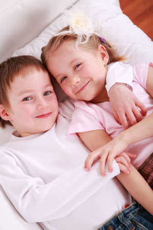 Cute twins lying together in bed photo