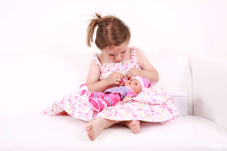 Beautiful small girl playing with doll Stock Photo