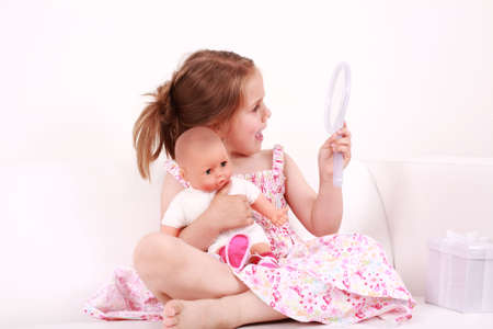 Beautiful small girl looking at the mirror