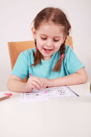 writing activity: Cute little girl painting at home
