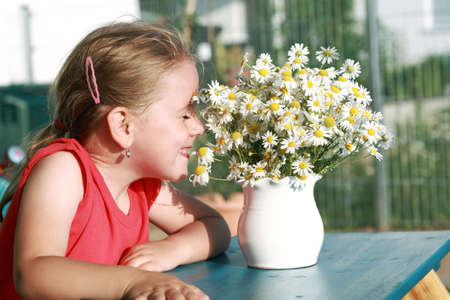 Little girl smelling chamomile bouquet