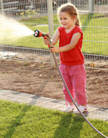 Little girl watering the grass in the garden photo
