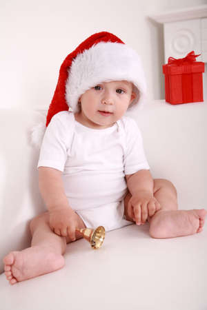 Lovely baby with Santa hat and Christmas bell photo