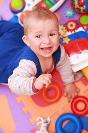 heartbreaking: Crying baby with lot of toys Stock Photo