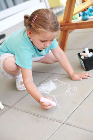 paiting: Little girl paiting with chalk - outdoors