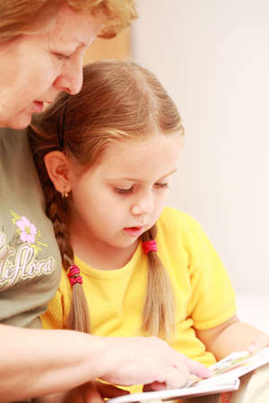 nana: Cute little girl reading a book with her grandmother Stock Photo